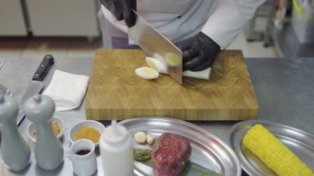 garlic : Chefs hands in black latex gloves cutting slices of lemon grass in cutting board. Kitchen table with kitchenware and ingredients. Corn, veal, sauses, garlic, different bottles, spices.