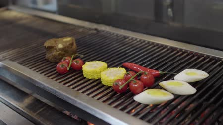 mısır koçanı : Hands of a chef putting vegetable on the grill in the restaurant kitchen close-up. Cook grilling corn, cherry tomatoes and lemongrass in the modern restaurant. Food preparation