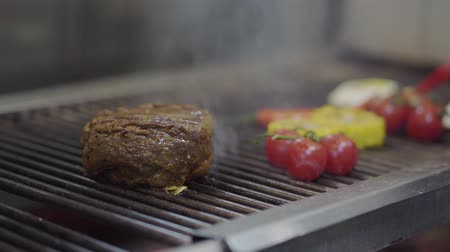 mısır koçanı : Chef cooking vegetable and meet on the grill in the restaurant kitchen close-up. Cook grilling meat, corn, cherry tomatoes and chili pepper in modern restaurant. Food preparation Stok Video