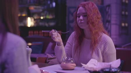 kisebbség : Two cute girlfriends have dinner in a modern restaurant together.