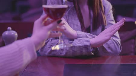 elutasít : Female hand holding glass with alcohol cocktail close up. Unrecognizable woman making refusal gestures, she does not want to drink alcohol. Unhealthy lifestyle