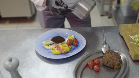 mısır koçanı : The chef pouring sauce on the plate with grilling meat, corn, cherry tomatoes, lemongrass and chili pepper lying there. Food preparation in the modern restaurant Stok Video