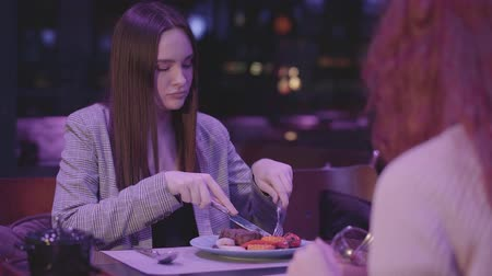 minoria : Two cute girlfriends have dinner in a modern restaurant together.