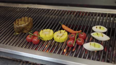 mısır koçanı : Unrecognized chef cooking vegetable on the grill in the restaurant kitchen close-up. Meat, corn, cherry tomatoes, lemongrass and chili pepper in the modern restaurant