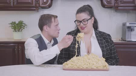 nerd : Portrait of a nerd guy and stylish bbw in glasses sitting at a table with a large plate of pasta in the kitchen. A man feeds his wife noodles. Funny relationship. Vídeos