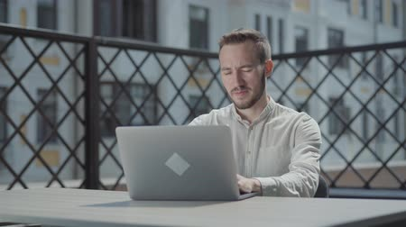 matter : Bearded young man sitting at the table on the terrace in front of the laptop, working. Concept of freelance, distant work. The guy doing business outdoors. Camera moving right Stock Footage