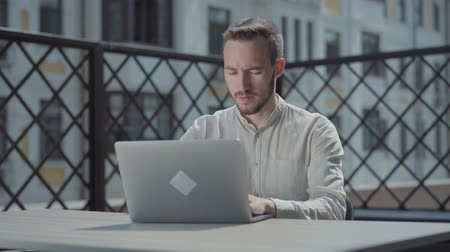 vzdálený : Bearded young man sitting at the table on the terrace in front of the laptop, working. Concept of freelance, distant work. The guy doing business outdoors. Camera moving right Dostupné videozáznamy