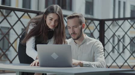 ohnutý : Bearded young man sitting at the table on the terrace in front of the laptop, working. Pretty girl bent near looking on the screen, smiling. Concept of freelance, distant work. The guy doing business