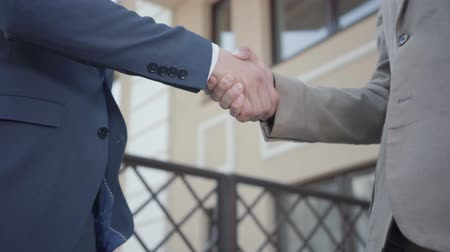 bastião : Two young man and female business partners shaking hands on the terrace close-up. Colleagues just made a good deal. Business relationship. Side view Stock Footage