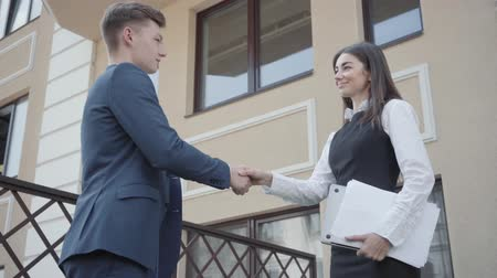 madde : Cute young woman and confident man in formal wear high five together on the terrace. Business relationship. Concept of freelance, team building