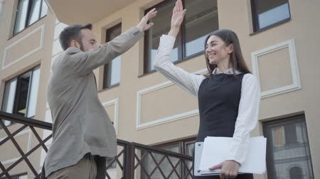 matter : Cute young woman and confident man in formal wear high five together on the terrace. Business relationship. Concept of freelance, team building