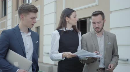 madde : Young woman and two men in formal wear walking on the terrace discussing the project. The girl nervous, she throwing up papers and walking away. Concept of freelance, distant work. The guys working outdoors Stok Video
