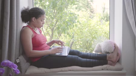 em casa : Young African American woman sitting on the window sill typing on her laptop. Happy girl relaxing at home alone. Day off of the lady. Side view