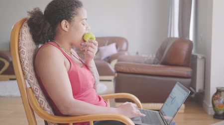 fauteuil : Pretty African American woman sitting on the armchair analyzing charts on her laptop while eating green apple close-up. Happy girl relaxing at home. Concept of distant work, freelance. Side view