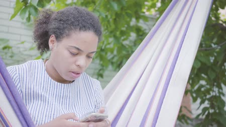 hamak : Young African American woman sitting in the hammock, relaxing in the garden, texting on cell phone. Leisure outdoors. Addiction to gadgets