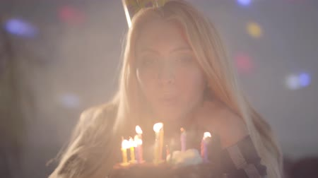 pesadelo : Portrait pretty blond woman blowing the candles on the cake. The lonely girl has birthday party. Concept of celebration Stock Footage