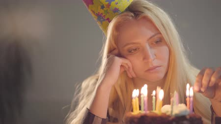 pesadelo : Lonely sad girl sitting in front of little cake lighting candles. An unhappy woman has a birthday party. Concept of depression, bad mood, loneliness