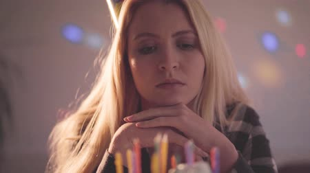 pesadelo : Lonely sad girl sitting in front of little cake with not lighted candles. Unhappy woman has a birthday party. Concept of depression, bad mood, loneliness. Camera moving right Stock Footage