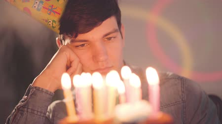 pesadelo : Lonely sad boy sitting in front of little cake with lighted candles looking on it. Unhappy man has a birthday party. Concept of depression, bad mood, loneliness. Camera moving right