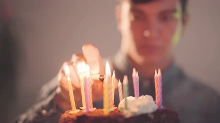 çakmak : The young man sitting in front of little cake lighting candles with the lighter. The lonely guy has a birthday party. Concept of celebration