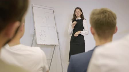 flip chart : A pretty young woman in formal wear lecturing in the office standing near the office board in front of people. Business meeting. The girl explains the material to colleagues