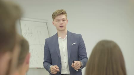 magyarázza : Young man in formal wear lecturing in the office standing near the office board in front of people. Business meeting. The guy explains the material to colleagues Stock mozgókép