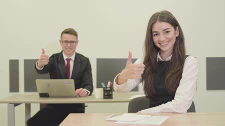 役員室 : Confident young male and female manager in the formal wear sitting at the desks in the office. The man and woman showing thumbs up smiling to the camera. Office life