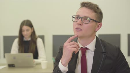 brifing : Portrait of a thoughtful young man in glasses sitting in the foreground in the office while his female colleague in formal wear working with laptop on the background. Office life, problem-solving Stok Video