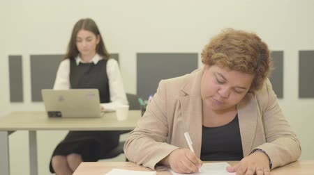 семинар : Young plump Filipina writing down information sitting in the modern office in the foreground while her slim pretty female colleague working with laptop in the background. Office life concept Стоковые видеозаписи