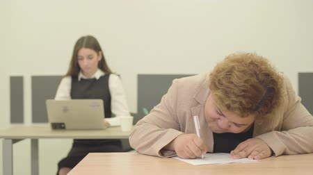 пухлый : Young plump Filipina writing down information sitting in the modern office in the foreground while her slim pretty female colleague working with laptop in the background. Office life concept Стоковые видеозаписи