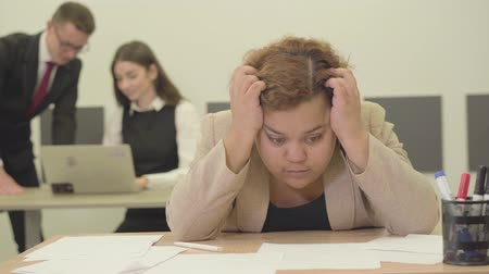flip chart : Nervous woman sitting at the table in the foreground holding her head with hands, she has trouble at work. Young confident man and woman in the background discussing the project on the laptop Stock Footage