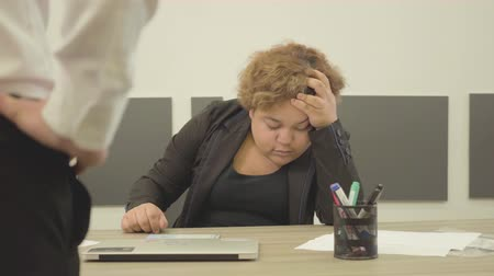 megijeszt : The plump tired woman sitting at the table in the office sleeping. An unrecognizable boss coming to the desk, and looking at her. The lady waking up and looking at the man. Office life concept Stock mozgókép