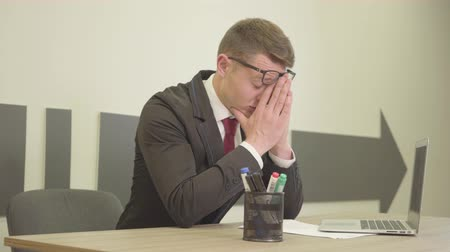 протирать : Young nervous stressed man in formal wear and glasses sitting in the office in front of the laptop rubbing his face. Stressful work, emotional instability