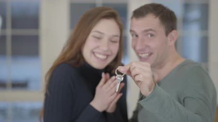 realty : Portrait of a happy married couple showing the keys of a purchased new house or apartment to the camera.