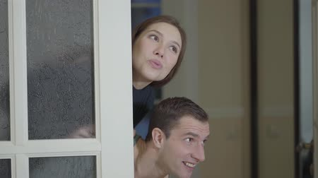 bérlet : Happy married couple inspects a newly purchased home or apartment. Smiling girl and boyfriend peeking out of the door. Stock mozgókép