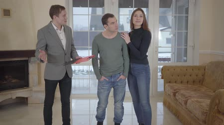 komisyoncu : Confident real estate agent shows a young successful married couple a new home. Happy man and woman looking around rented bought residence