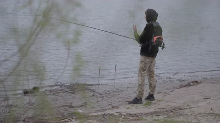 khaki : Confident young fisherman in khaki pants in the early morning spinning fishing in river near the city