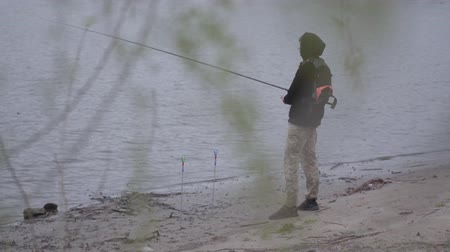 dacha : Confident young fisherman in khaki pants in the early morning spinning fishing in river near the city