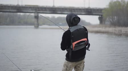 снасти : Angler or fisherman in khaki pants in the early morning catch scomber fish with spinning in river near the city
