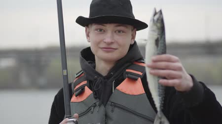 piada : Young confident happy fisherman wearing a cap with a brim in the early morning catch fand showing fish looking to camera. Stylish fisherman on holidays on river, relaxing and fishing trout.