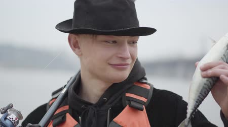 снасти : Young confident happy fisherman wearing a cap with a brim in the early morning catch fand showing fish looking to camera. Stylish fisherman on holidays on river, relaxing and fishing trout.