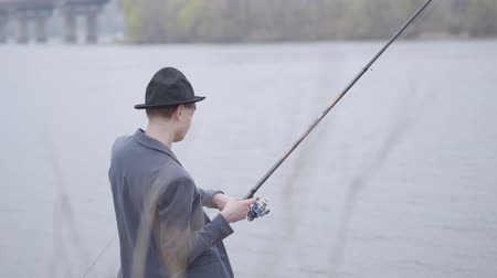 fisher : Young fisherman in a jacket and a cap with a brim in the early morning fishing in river near the city. Fishing rod and a reel. Fly fisher on the river