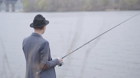 dacha : Young fisherman in a jacket and a cap with a brim in the early morning fishing in river near the city. Fishing rod and a reel. Fly fisher on the river