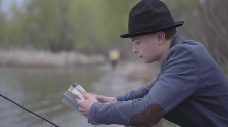 dacha : Portrait stylish fisherman in a jacket and field cap sits near a river and reads a book or fishing tips for fishing with fishing rods Stock Footage
