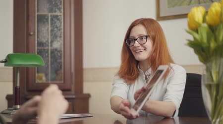 gyógyász : Attractive red-haired young female psychologist in glasses consulting her male patient, showing information on the tablet, smiling. Psychotherapy session Stock mozgókép