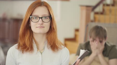 сосредоточиться на переднем плане : Confident woman in glasses looking in camera in the foreground. Blured figure of young depressed man sitting in the office of a psychologist, holding fluffy pillow, crying on the background. Psychotherapy session Стоковые видеозаписи