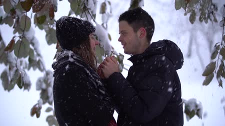 contato com os olhos : Beautiful young woman and man looking into each others eyes. in winter park under falling snow. Man warms hands of lady. Happy couple in love enjoys time together. Winter leisure. Slow motion