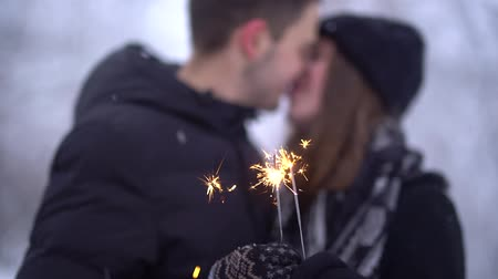 bengália : Blurred figures of young man and woman kissing in the background of burning sparkler in snow covered park outdoors. Winter leisure of happy loving couple. Slow motion