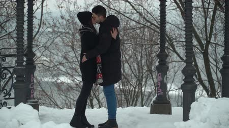 contato com os olhos : Beautiful young woman and man kissing passionately in winter park covered with snow Happy couple in love enjoy time together. Winter leisure. Camera moves closer, zooming