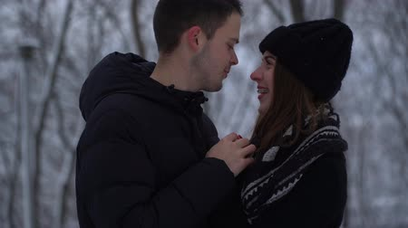 contato com os olhos : Portrait cute young woman and man talk looking into each others eyes in winter park. Man warms hands of lady. Happy couple in love enjoys time together
